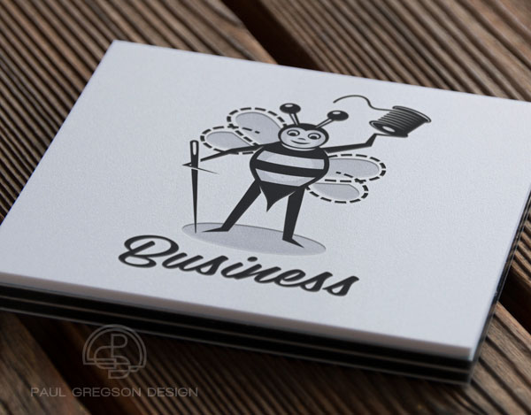 sewing bee character logo on pressed card stock